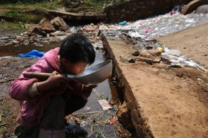 A child drinks water near a stream in Fuyuan county, Yunnan province March 20, 2009. World Water Day will be observed on March 22. Picture taken March 20, 2009. REUTERS/Stringer (CHINA ENVIRONMENT IMAGE OF THE DAY TOP PICTURE) - RTXD19C